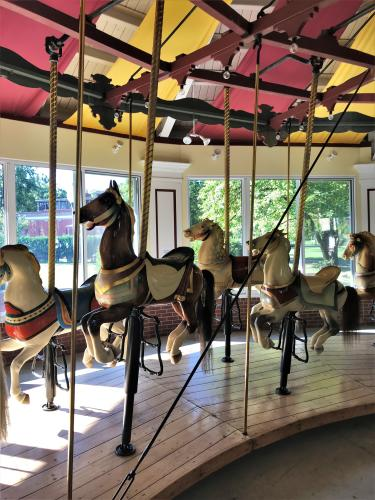 Several carousel horses with red and yellow ceiling