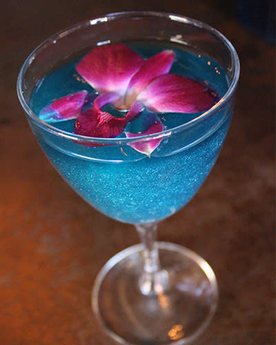 Blue shimmering cocktail drink garnished with orchid flower.