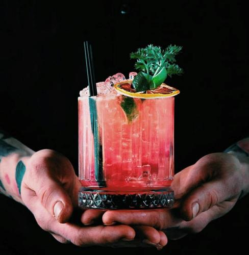 The Night Owl pink cocktail with garnish and straw being held in two hands with black background
