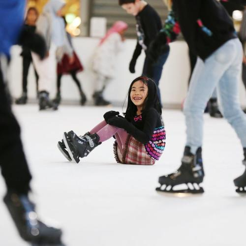 A little girl sitting in the middle of a skating rink while people skate around her