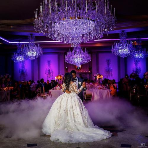 Bride and groom dancing under chandeliers in dark room lit in purple lights with mist on the ground