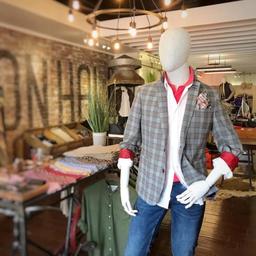 Male mannequin dressed in jeans and layered tops with exposed brick wall in the background