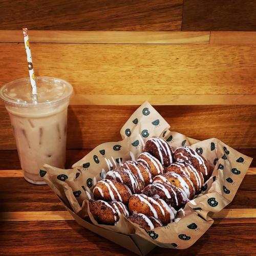 Basket of donut holes drizzled with icing and an iced coffee