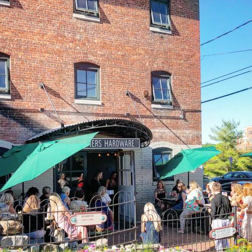 Group of people surrounded by Farmers Hardware entrance and patio with green umbrellas