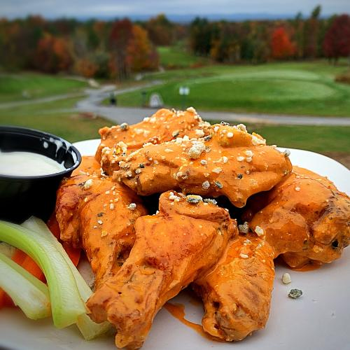 Chicken wings on a white plate with the golf course in the background.