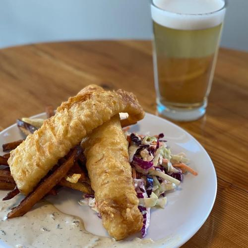 Fried Fish over Slaw on a white plate sitting on a wooden table with a glass of pale frothy beer