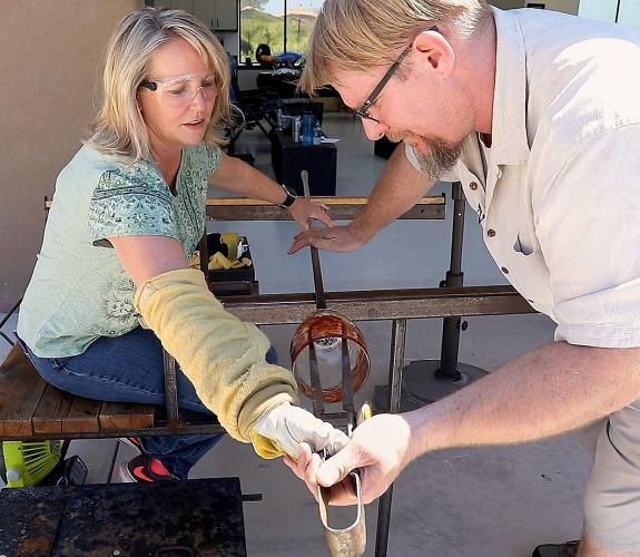Gregory T. Glass Blowing studio working with a customer