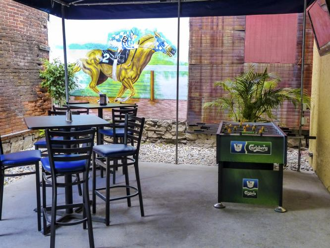 Black patio seating infront of thoroughbred horse racing decal on brick wall at Peabody's patio in Saratoga Springs NY