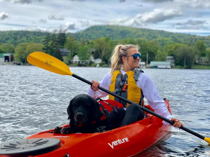 Woman and dog kayaking through lake george