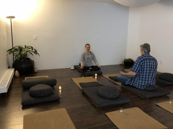 Two people meditating in a studio