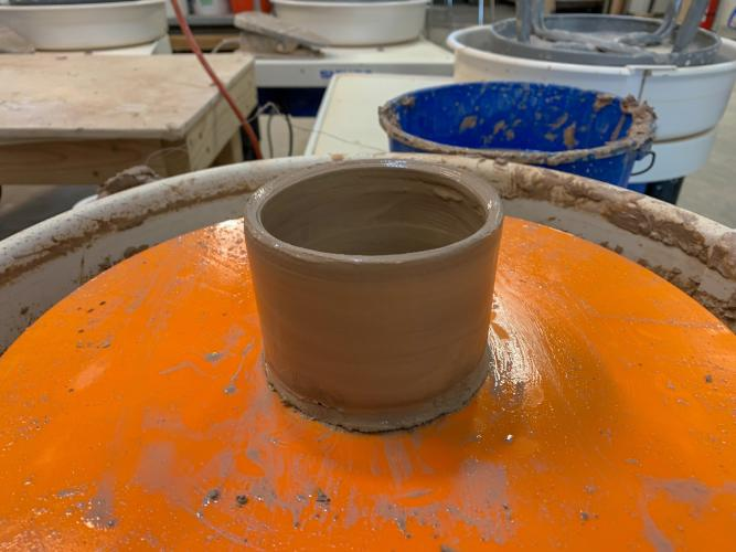 Small and wet clay cup on Potter's Wheel