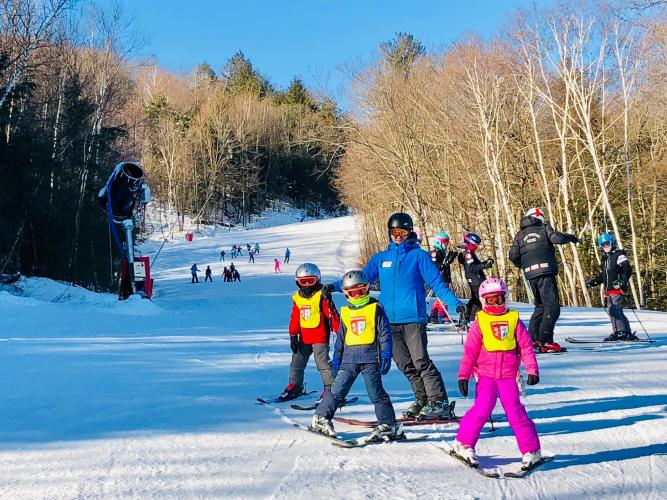West Mtn. father and 3 kids on skis on the slope