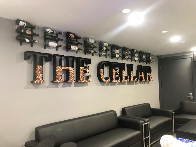 The Cellar wall sign with wine bottles displayed over it and black couches underneath