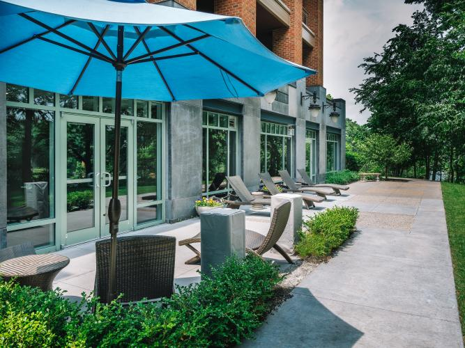 Empty patio with blue umbrella on a sunny day at Complexions in Saratoga Springs, NY