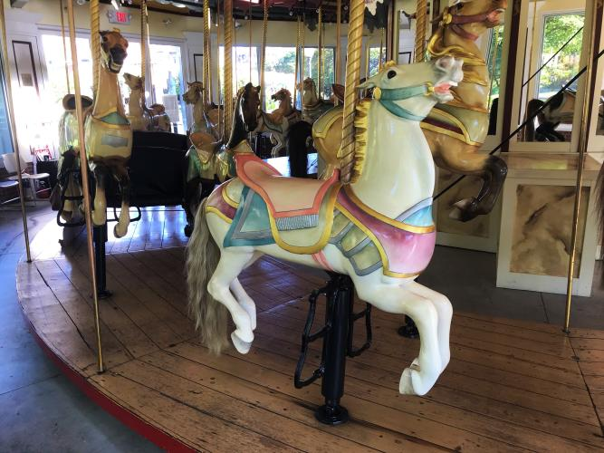 Closeup of a white carousel horse with pink saddle