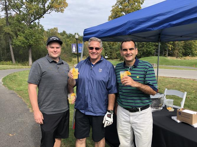 Three golfers posing with their drinks in front of a blue tent.
