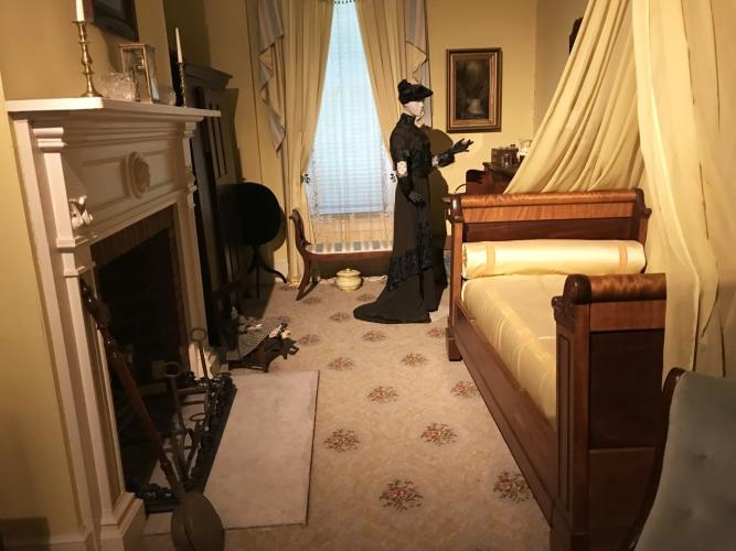 Walworth Mansion bedroom exhibit with woman standing by bed in yellow room with large fireplace