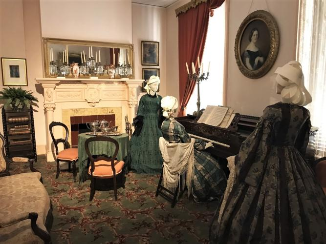 Walworth Mansion in piano room with 3 women standing around piano