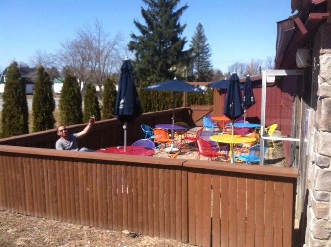 Picture of guy holding up a beer with colorful tables and chairs at King Tavern's patio