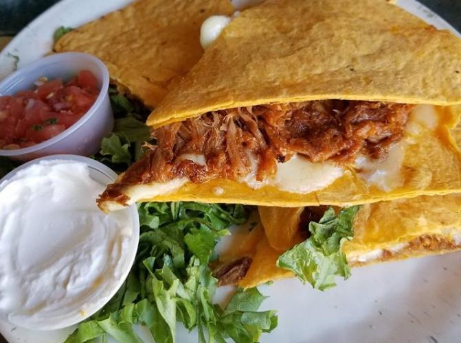 Carnitas quesadilla with sides of sour cream and salsa