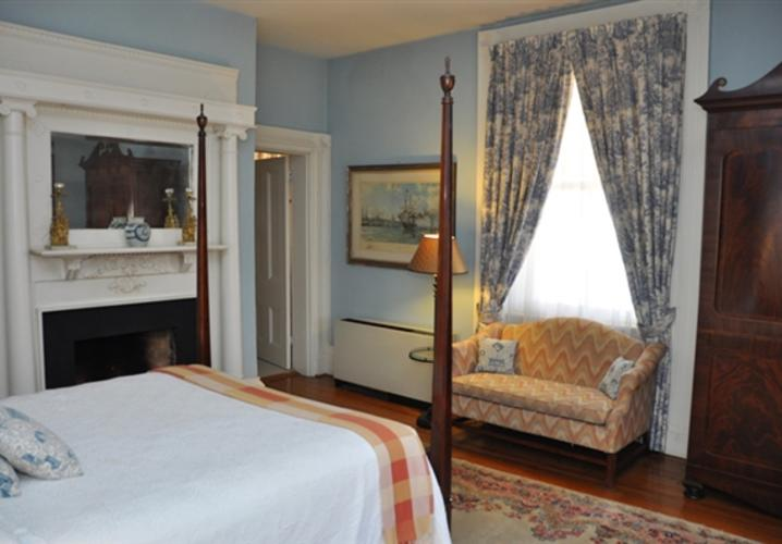 This former parlor of the Main House features an elaborate fireplace and a four poster bed.