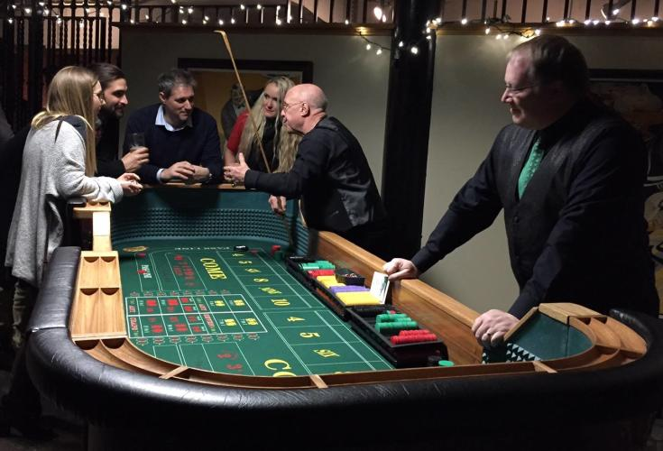 Alpine Amusement Group of people around a gaming table placing their bets.