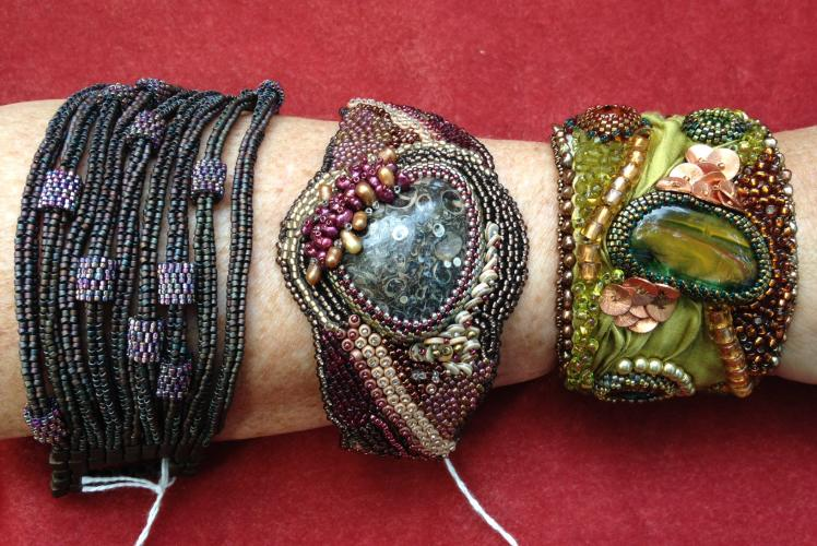 three different types of bracelets, bangle, leather backed cuff and a metal back cuff