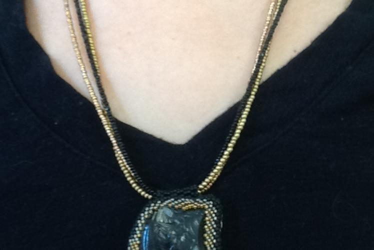 necklace with a bezeled river rock in black and gold beaded chain
