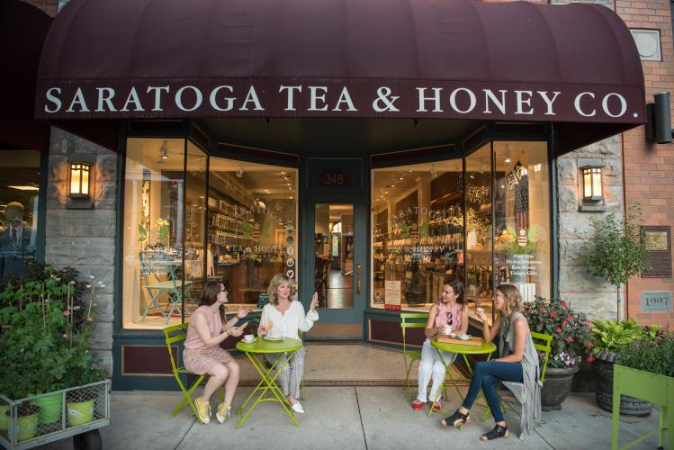 Group of 4 people enjoying tea and sitting on green chairs outside of Saratoga Tea & Honey