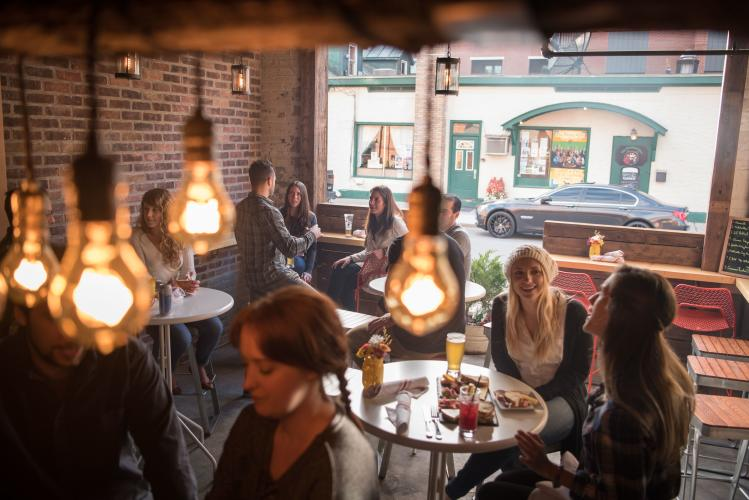 Group of people dining at Henry Street Taproom in Saratoga Springs with focus on lightbulbs