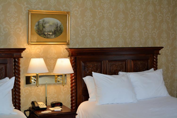Inn at Saratoga room with twin beds, lamps and framed print