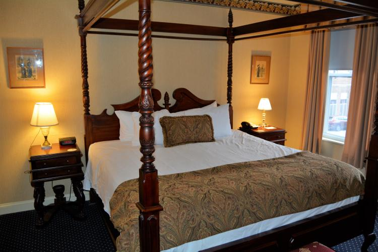 Large four poster bed with coverlet across the foot of bed