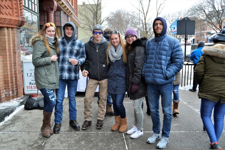 Group of attendees posing on sidewalk