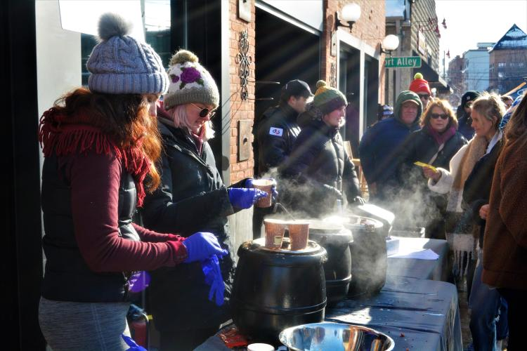 Girls serving steaming chowder in the sunlight