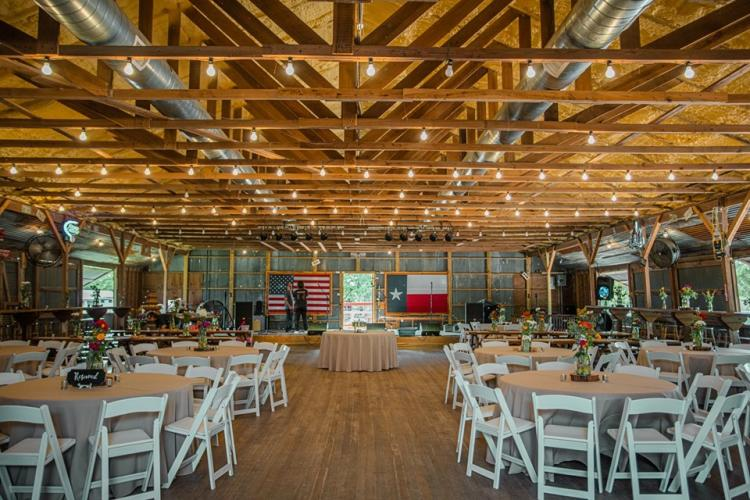 Wedding Venue Set up with chairs, lights in the rafters, and a stage