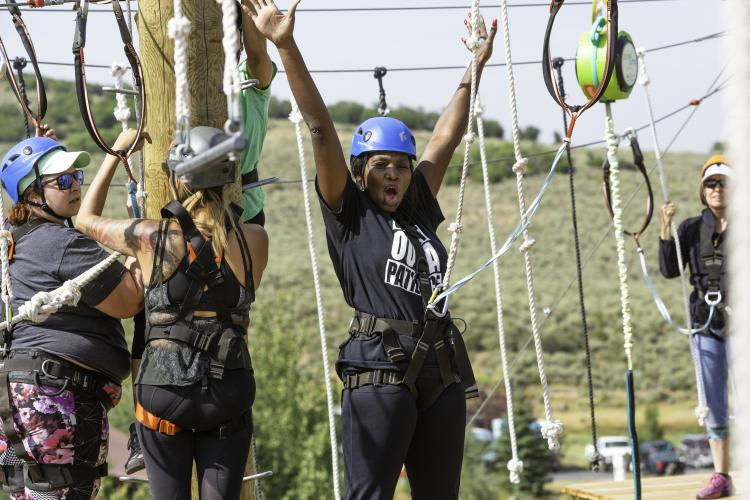 Woman cheering after completing ropes course at the National Ability Center in Park City