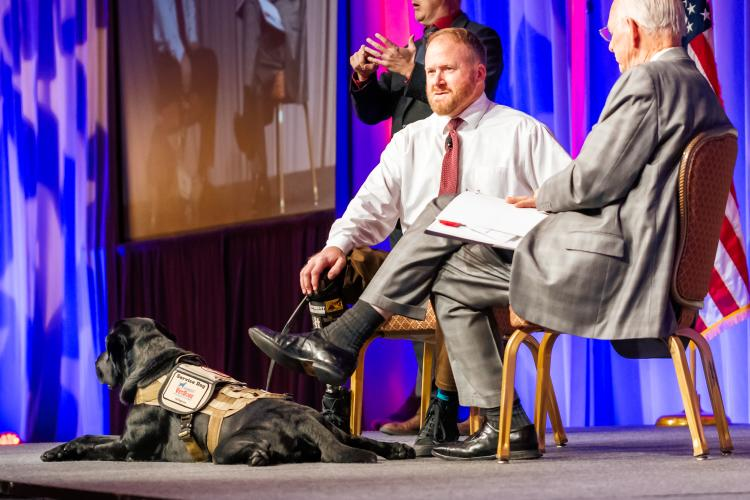 Two People speaking on a stage with a service dog laying down next to them