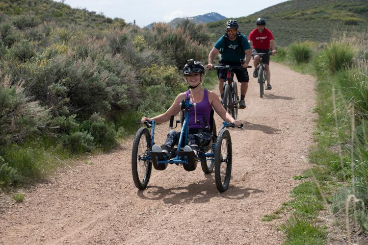 Woman and two men riding on 4 cross mountain bikes in Park City, UT