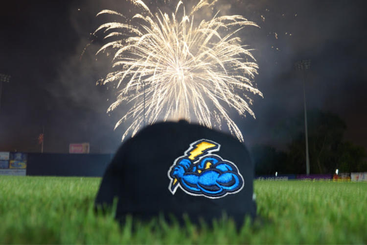 Baseball cap with Trenton Thunder Baseball team logo placed on grass of baseball field. Fireworks exploding in the distance.