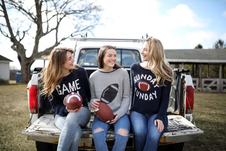 Three young women sitting on the tailgate of a truck holding footballs and wearing football themed sweaters