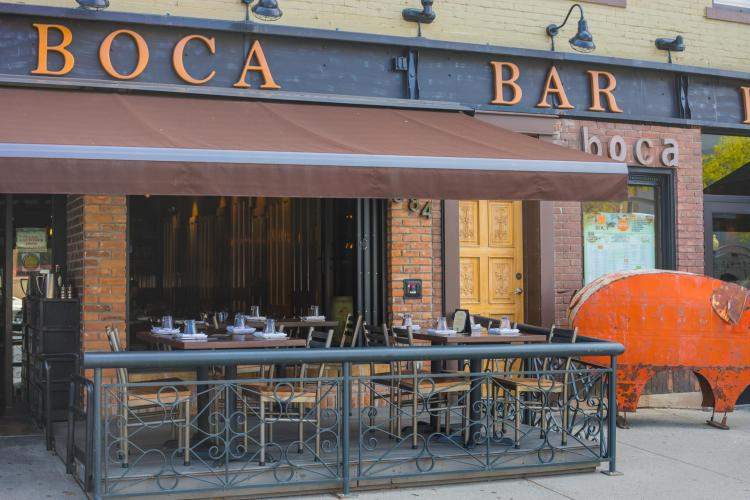 Empty tables and chairs at Boca Bistro's patio with orange metal pig