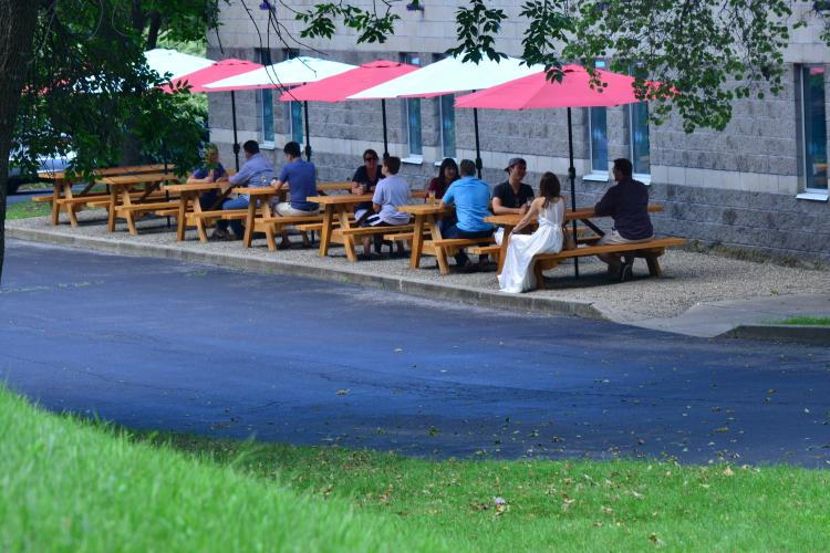 Far away shot of people sitting on patio furniture at Racing City Brewery