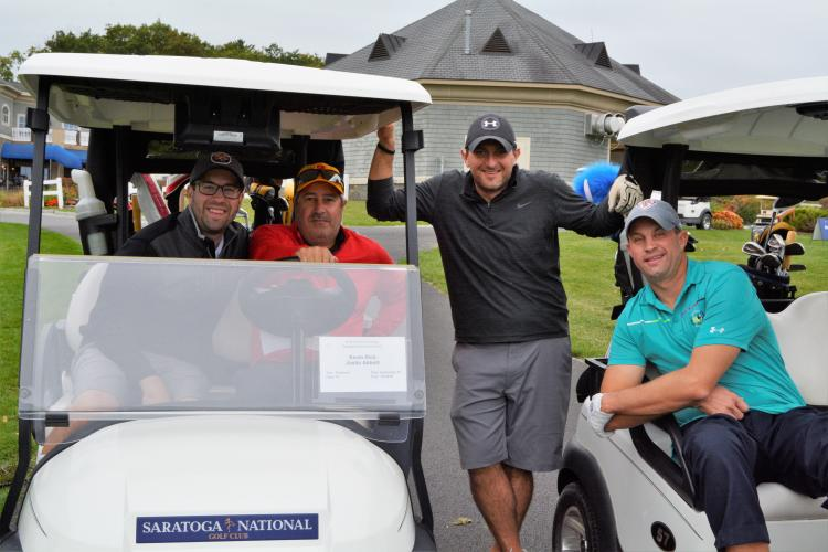Foursome posing with two men in a golf cart, one standing in between carts and one hanging out the side of the other