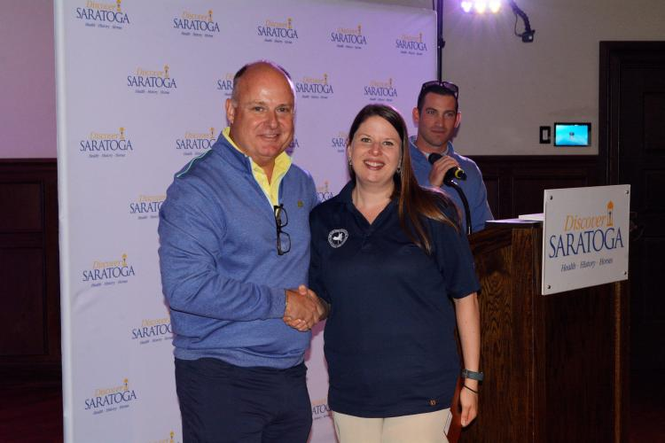 Darryl shaking female golf award winner's hand in front of the Discover Saratoga backdrop