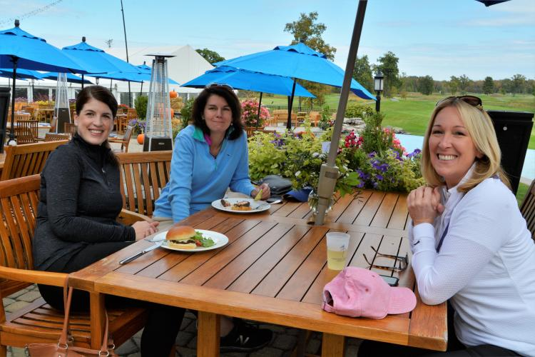 3 women sitting on patio at table at National under blue umbrella