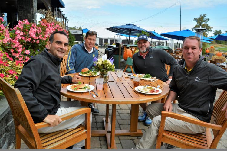 Four guys sitting at a table eating lunch on the patio at National