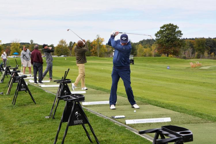 Four golfers lined up at the driving range taking practice swings