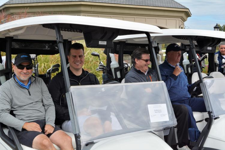 Foursome of guys sitting in two golf carts