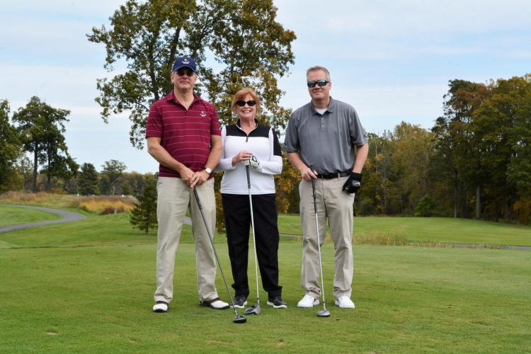 Thomas Olsen and two others standing together holding golf clubs in front of them for pose