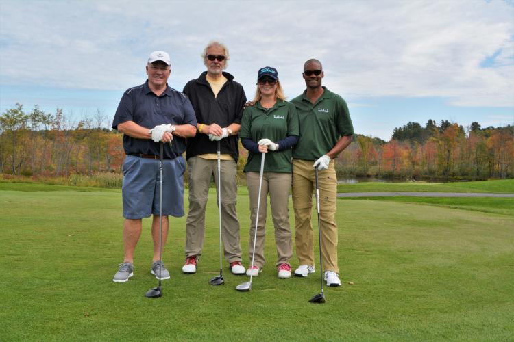 Foursome from the Saratoga Hampton Inn standing side by side with golf clubs in front of them.